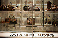 Handbags and women's shoes are featured in the window of the Michael Kors store on Fifth Avenue in New York on Monday, September 26, 2011. Despite the current recession products that are considered affordable luxuries are defying the economy, while the sales of staples, such as thermometers, vacuum bags, etc. are dropping. (© Richard B. Levine)