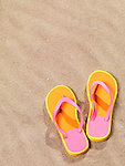 Close up of a pair of orange flip flops on beach sand background