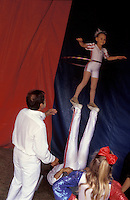 "Circus family trains young children for acrobatic act. Bentley Bros. circus, one of the few remaining ""mud show"" circus performing under a canvas big top."