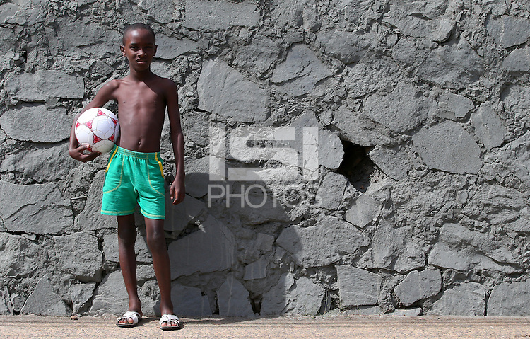 A young Brazilian boy holds his football in Salvador, one of the 12 host cities of the 2014 FIFA World Cup