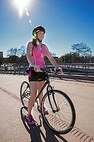 Attractive female biker on Lamar Street Pedestrian Bridge ponders her mountain biking excursion on the Lady Bird Lake Hike and Bike Trail in downtown Austin, Texas.