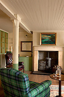 In a corner of the tasting room an armchair covered in emerald green-and-black tartan seems to echo the colours of the landscape seen in an oil painting above the fireplace