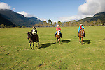 Chile, Lake Country: People riding horses at Peulla in a meadow in the Andes..Photo #: ch603-33250..Photo copyright Lee Foster www.fostertravel.com, lee@fostertravel.com, 510-549-2202.