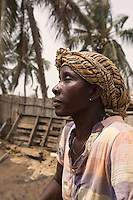 Ghana - Fuveme - Janeth Akorli, 46, sits on the premises of her house, which was partially damaged by high tide the day before. « I was cooking when the water entered the house. I couldn't do anything, apart from saving some of my belongings », she explains. A widow and mother of three children, Akorli struggles to carry on in this challenging situation. « I am afraid of the sea now. I should leave, but I have nowhere to go. »