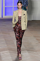 Ruby Aldridge walks the runway in a khaki cotton canvas double-breasted suit jacket, red camouflage silk button-front camisole, and red camouflage silk pleated cigarette pants with ankle straps, by Tommy Hilfiger for the Tommy Hilfiger Spring 2012 Pop Prep Collection, during Mercedes-Benz Fashion Week Spring 2012.