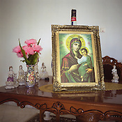 A religious icon stands , propped against a bottle of whisky, on a table top in a Roma house in the new part of the Sintesti Roma camp. The Roma are Romanian Orthodox in religion...