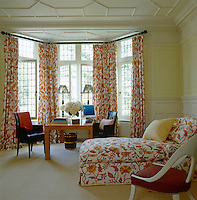 A chaise longue upholstered to match the curtains in the bay window of a guest room