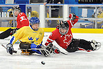 Marc Dorion (7) chases the puck during 2010 Paralympic Games sledge hockey action at UBC Thunderbird Arena in Vancouver. Credit: CPC/HC/Matthew Manor.