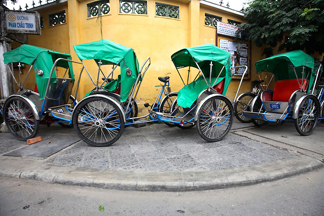 A group of cyclos is parked on a street corner one early morning in Hoi An, Vietnam. The pedicabs are a popular means of transporting tourists through the streets of the quaint colonial city. April 22, 2012.