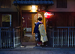 Geisha enters Japanese tea house - or ochaya to provide the evenings entertainment in the Gion district of Kyoto