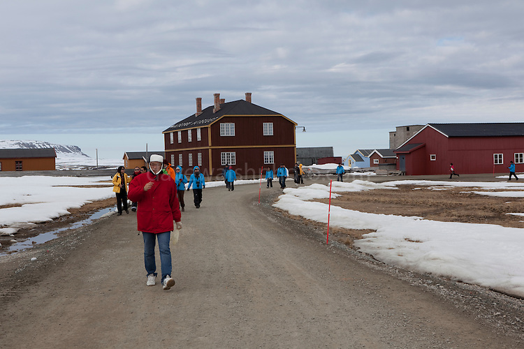 Chinese tourists walk pas the North Pole Hotel whle visiting the international scientific research base at Ny Alesund, Svalbard, while travelling on board the Hurtigruten cruise ship Fram.