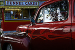 .This 1940 Ford looks at home next to a Funnel Cakes stand at the Iowa State Fairgrounds...Cars and their owners were in Des Moines over the 4th of July weekend for the Good Guys 16th Heartland Nationals held at the Iowa State Fairgrounds, bringing over 3,500 of the country?s hottest rods and coolest customs to Iowa?s Capital City.  ..Exhibitors are very skilled, multi-talented craftsmen. They dedicate thousands of hours to bring their hot rod or custom  autos to a high standard. Unlike many car shows the Good Guys usually drive both to and from the event...Photo by David Peterson