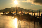 Sunrise on Lake Coeur D Alene silhouettes boats at a marina