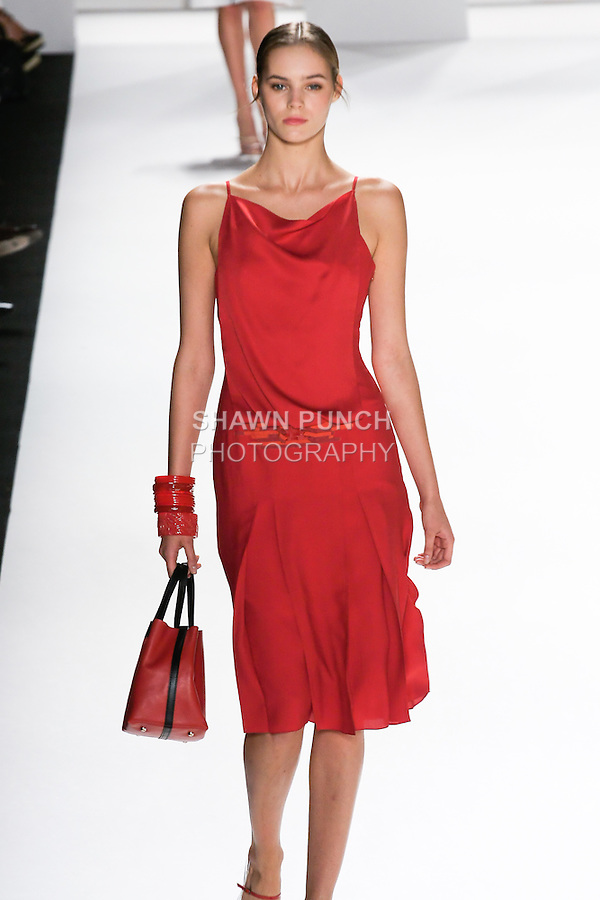 Juju Ivanyuk walks the runway in a red seersucker silk cloque dress, red Matryoshka handbag for the Carolina Herrera Spring 2012 fashion show, during Mercedes-Benz Fashion Week Spring 2012.
