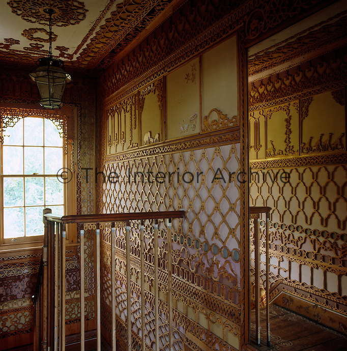 A mirror on the landing wall reflects the ornamental fretwork covering the walls