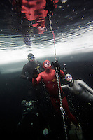 Bjarte Nygard of Norway about to surface, followed by safety divers and judge. Freediving competition Oslo Ice Challenge at freshwater lake Lutvann outside the Norwegian capital Oslo. Atheletes, including current and former world champions, entered a hole in the ice to compete. The participants reached depths down to 52 meters below the surface.