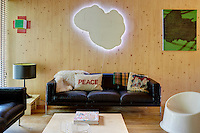 The artist Richard Woods has built a timber house where he can both create and showcase his bold, bright work. The scent of timber pervades the interior with floors of solid oak and walls constructed from cross laminated timber panels. The sitting room displays artworks and design classics. The black leather sofas are by Robin Day and the white plastic chair is by Verner Panton.
