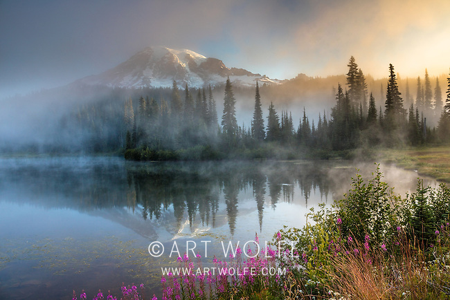 Mount Rainier appears as mist rises off a lake at dawn, Mt. Rainier National Park, Washington, USA