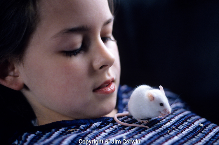 Young girl holding a pet mouse sitting on girls chest eating seeds