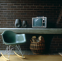 A glass-fibre Eames rocking chair stands infront of a concrete table against a dark brick wall