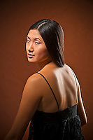Young Asian woman, seated, rear view