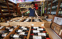 A wine trader holds a 1.5 litre bottle of Moulin de Duhart Paulliac 2009 which sells for RMB7,330.00 at the official Chinese government-owned Guangzhou Friendship Store across town. But she was selling it for just RMB1,230.00 &ndash; about a hundred pounds.<br /> <br /> PHOTO BY SINOPIX
