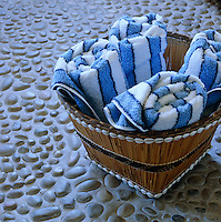 An African basket from Mark Valentine on the pebble floor of the bathroom is filled with blue and white striped towels