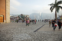 Early evening at the Tsim Sha Tsui waterfront in Kowloon, between the Star Ferry terminal and the 1915 Clock Tower; the skyscrapers of Hong Kong's Central business district can be seen across the harbour
