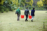 three gardeners carry 2 red buckets of water among them as they pass through a grove heading to their planting site in Guilin, China