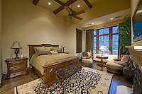 Bedroom with traditional furniture, cross-beamed ceiling, and large paned window
