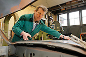 Adrian Rice, panel beater, working on the resoration of a Jaguar XK 120.  First he builds a wooden formwork then makes new aluminium panels to fit it.  Once the panels are fixed in position, the wooden formwork is removed.