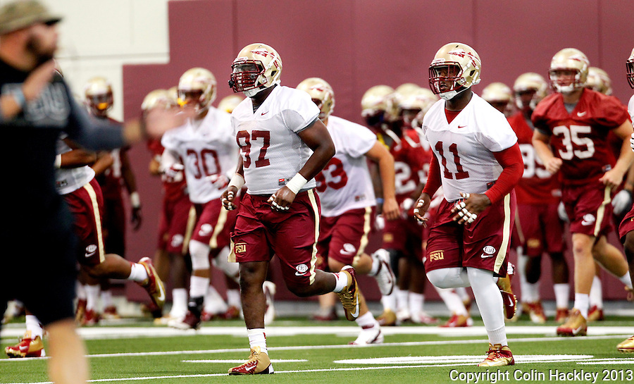 TALLAHASSEE, FLA.8/6/13-FSU080613CH-The Florida State's Demonte McAllister, center, and Derrick Mitchell run in the Seminole's new indoor practice facility for the first time, Aug. 6, 2013 in Tallahassee, Fla.<br /> <br /> COLIN HACKLEY PHOTO