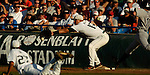 06/19/2006 Miami pitcher Danny Gil dives towards first while making an errant throw to Yonder Alonso as Rice University's Danny Lehmann legs it out during game eight of the College World Series in Omaha Nebraska Monday evening..(photo by Chris Machian/Prairie Pixel Group)