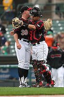 Catcher Juan Centeno (59) and closer J.R. Graham (39) of the Rochester Red Wings hug to celebrate a win against the Scranton Wilkes-Barre Railriders on May 1, 2016 at Frontier Field in Rochester, New York. Red Wings won 1-0.  (Christopher Cecere/Four Seam Images)