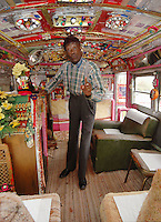 "Reverend Dennis points out the need for prayer to all those who stop by his roadside ""Palace"" and church. The 90 year old Rev. Dennis has lovingly turned a broken down school bus into a church, and he spreads the gospel to all that stop by to visit him and his wife Miss Margaret at their home on Highway 61 in Vicksburg Mississippi. (Photo/Suzi Altman)"