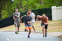 Coolangatta, Queensland, Australia. (Tuesday February 18, 2014) –  The current World Surfing Champion Mick Fanning (AUS) and Leo Fioravanti (ITA) running hills during a training session with Fanning's coach Nam Baldwin (AUS) at Coolangatta, and being filmed for a TV show in Italy.  Photo: joliphotos.com