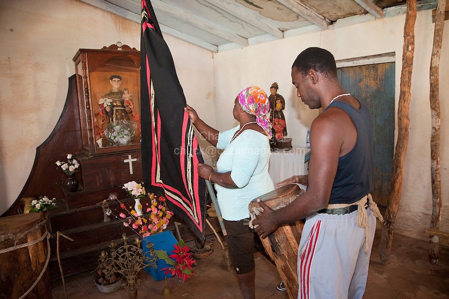 Cuba, Trinidad.  Woman Raising Flag in front of Shrine to Saint Anthony (San Antonio) while Performing an Afro-Cuban Religious Ceremony.