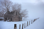 Idaho,Central,New Meadows. An abandoned and rustic house with collapsed roof and fence in a foggy, snow covered landscape at dawn in winter.