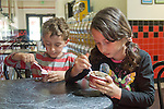 Berkeley CA Siblings, five and seven, concentrating on eating ice cream covered with chosen toppings  MR