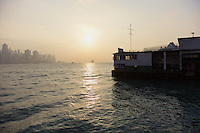 View at sunset from the Star Ferry (Tsim Sha Tsui) pier across the harbour to Central Hong Kong. A cruise ship and a traditional Chinese junk can be seen on the water.