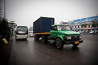 Daytime landscape view of a truck pulling a storage container near the Sānménxiá Shì Húbīn District in Hénán Province.  © LAN