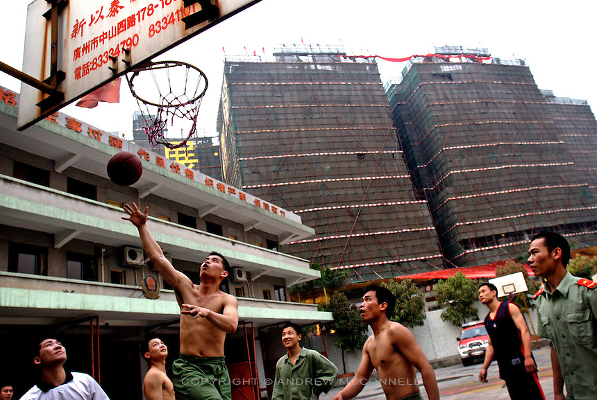 Local fire fighters relax by playing basketball in the shadow of another of Guangzhou's massive construction projects.