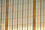 Detail image of warm-toned, glass-clad commercial high rise building, with cloud reflections.