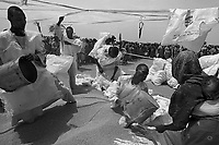 Habila, West Darfur, August 10, 2004.IDP beneficiaries of a WFP food distribution operation after a plane airdrop. More than 140 metric tons of food in 2800 50 Kg bags have been dropped in one day from four big Yliuchin cargo planes. During the month of July 2004 alone, the WFP distributed food to more than 951 000 people in Darfur.