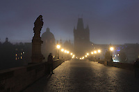 The Charles Bridge or Karluv most at night, built 1357 - 15th century, looking towards the Old Town bridge tower, across the Vltava river in Prague, Czech Republic. Its construction began under King Charles IV, replacing the old Judith Bridge built 1158'??1172 after flood damage in 1342. This new bridge was originally called the Stone Bridge (Kamenny most) or the Prague Bridge (Prazsky most) but has been the Charles Bridge since 1870. The bridge is 621m long and nearly 10m wide, resting on 16 arches shielded by ice guards. It is protected by three bridge towers, two on the Lesser Quarter side and one in Gothic style on the Old Town side. The historic centre of Prague was declared a UNESCO World Heritage Site in 1992. Picture by Manuel Cohen