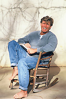 Man smiling outdoors in a wooden rocking chair