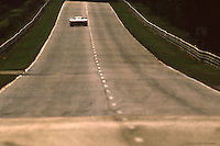 One car races away from the exit of Mulsanne Corner, late afternoon, during the 1985 24 Hours of Le Mans auto race.