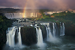 In 1986, UNESCO declared Iguazu Falls a World Heritage Site. The falls is a part of Iguazú National Park in Argentina. Early sun illuminates the mist rising from the falls, creating a partial rainbow.