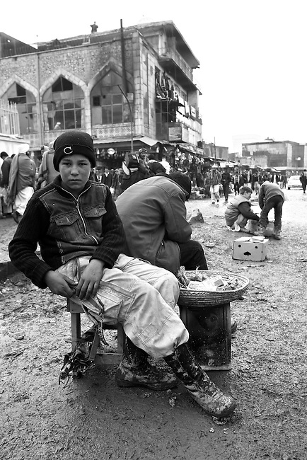 A boy pockets his money after a transaction in the central market of Kabul, Afghanistan. Despite the ever-present mud and miserable winter weather, the market bustles daily with commerce of all kinds. Taliban attacks in the Afghan capital have so far been infrequent, and as life goes on at a normal pace, the war often seems far away. Feb. 3, 2009.