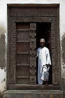 Zanzibar, Tanzania.  An Arab-style Doorway in Stone Town.  An African Zanzibari Wearing Traditional Kanzu and Kofia (Hat) Stands in the Doorway.